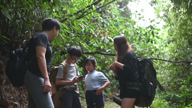 an asian chinese family of 2 children standing in front of the tropical rainforest in the morning checking on map using smart phone navigation
