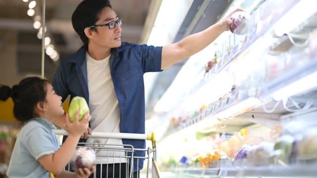 アジアの中国人の父と娘が食料品店の冷蔵庫野菜部門で買い物をする野菜を選んで買う - 小売り点の映像素材/bロール