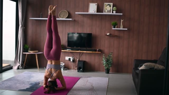 una femmina cinese asiatica che pratica yoga in soggiorno domestico utilizzando laptop per la lezione online - posizione corretta video stock e b–roll
