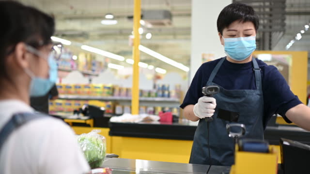 An asian chinese female supermarket retailer shop assistant cashier scanning vegetable for the pricing during checkout at counter