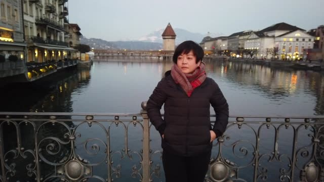 an asian chinese female tourist at the bridge of old town feeling cold during dusk
