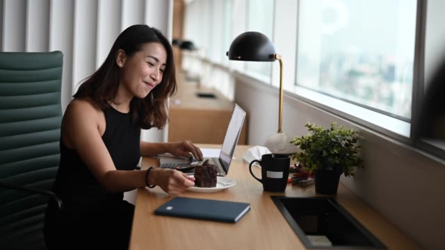 an asian chinese female white collar worker young executive enjoying her chocholate cake while working at her workstation in co-sharing working office in the afternoon with social distancing applied
