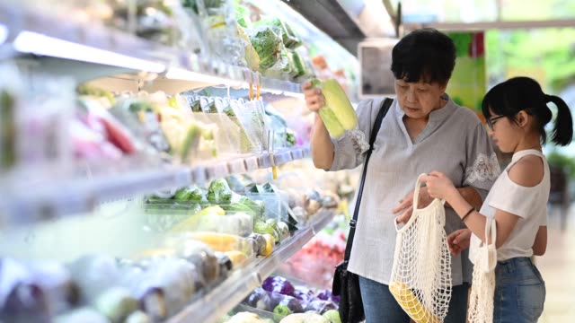 an asian chinese grandmother and granddaughter shopping in a grocery shop refrigerator vegetables department selecting and buying vegetables