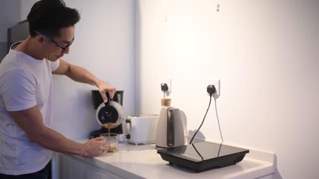 азиатский китайский мужчина наливает кофе на своей кухне - кофеин стоковые видео и кадры b-roll