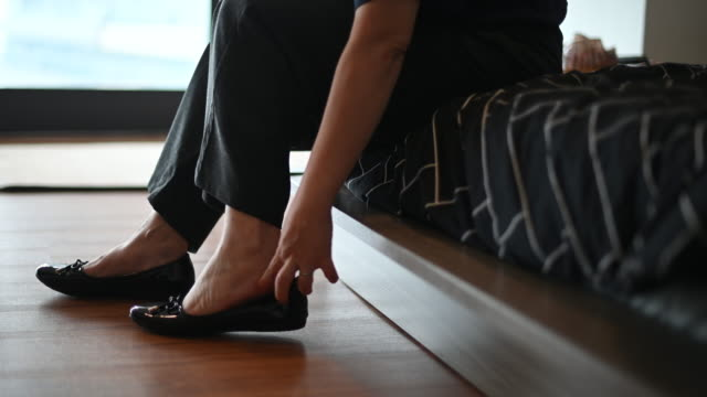 an asian chinese mid adult is getting ready wearing her shoes before leaving her apartment to work an asian chinese mid adult is getting ready wearing her shoes before leaving her apartment shoe stock videos & royalty-free footage