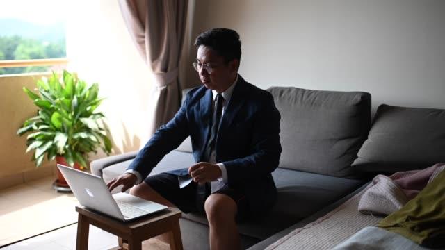 un uomo di mezzo adulto cinese asiatico con cravatta e tuta e pantaloni corti seduti sul divano usando laptop nel suo soggiorno per videoconferenza con il suo socio in affari e collega incontro di lavoro virtuale - pantaloncini video stock e b–roll
