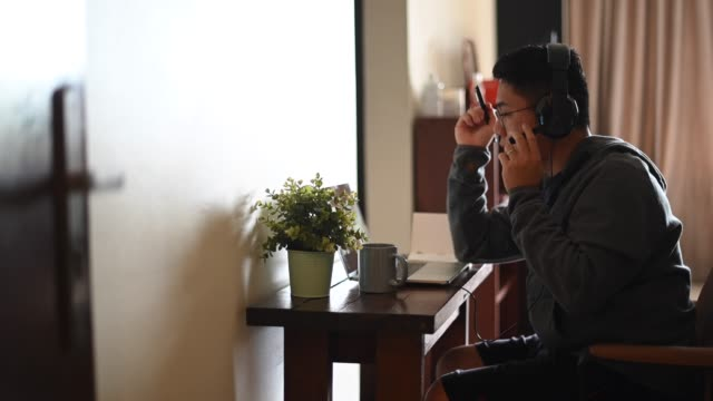 an asian chinese mid adult man working from home with his new home office setup at living room