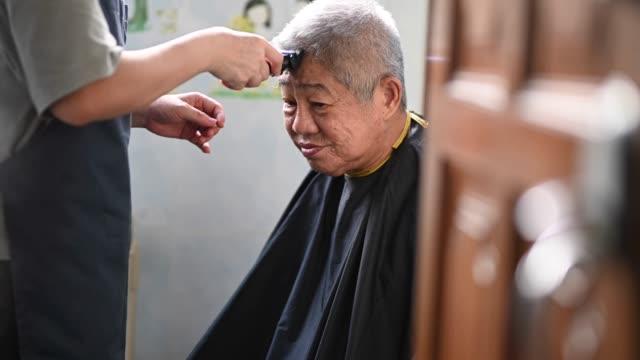 vidéos et rushes de une femme chinoise asiatique mi adulte est la coupe et la coupe des cheveux pour son père dans la cuisine en raison de l'interdiction de voyager - salons et coiffeurs