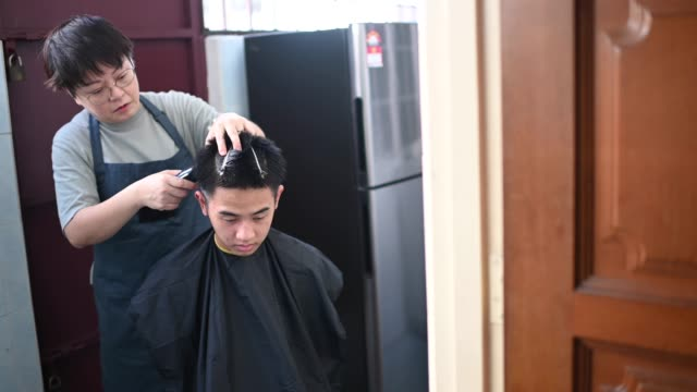 an asian chinese mid adult woman is cutting and trimming hair for her son in the kitchen due to travel ban