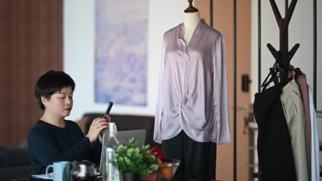 an asian chinese mid adult woman photographing and recording cloth for online shopping business catalog in her dining room