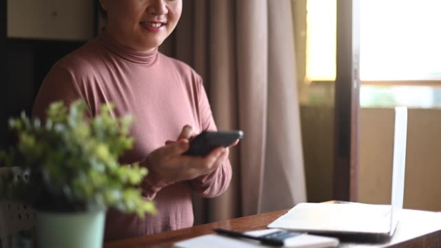 an asian chinese mid adult woman using her laptop and credit card for online shopping