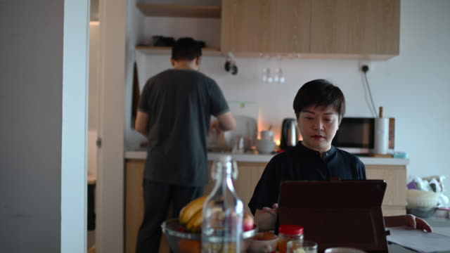 an asian chinese mid adult woman working from home at dining table using digital tablet and documents during breakfast time while her husband cleaning dishes