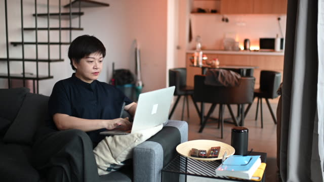 an asian chinese mid adult woman working from home at sofa living room using laptop and documents during morning - new normal video stock e b–roll