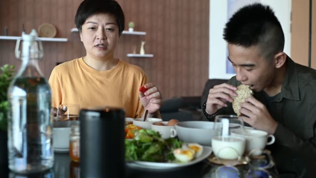 an asian chinese mother having healthy breakfast with her teenager son in dining room in the morning bonding time while using virtual assistant smart speaker checking morning news from radio station - assistente virtuale video stock e b–roll