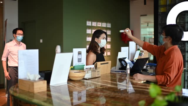 an Asian Chinese receptionist conducting standard operating procedure for illness prevention by measuring visitors colleague coworkers body temperature and record their personal data