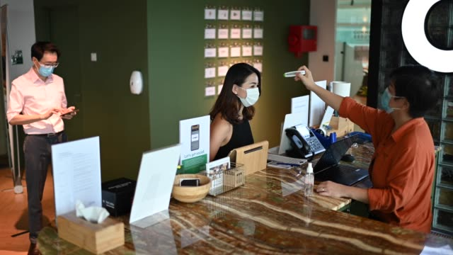 an asian chinese receptionist conducting standard operating procedure for illness prevention by measuring visitors colleague coworkers body temperature and record their personal data - hotel checkin video stock e b–roll