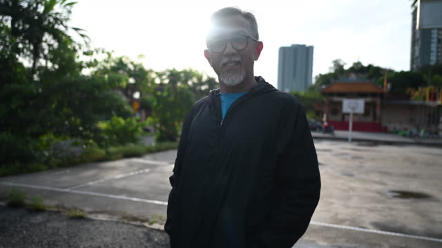an asian chinese senior man coach in the morning wearing windbreaker at basketball court getting ready to practice and exercising