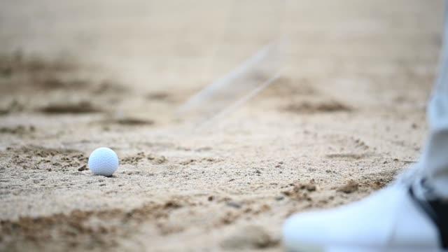 vídeos de stock, filmes e b-roll de um golfista chinês asiático batendo sua bola de golfe em uma armadilha de areia com seu taco de ferro - exatidão