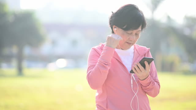 an asian chinese senior woman exercising in the public park in morning selecting songs from her smart phone for listening before start her exercise