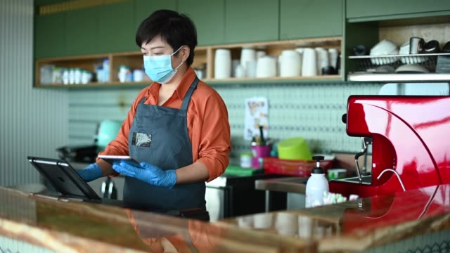 an asian chinese small business owner with face mask and protective gloves keying in check out payment an asian chinese small business owner with face mask and protective gloves keying in check out payment wait staff stock videos & royalty-free footage