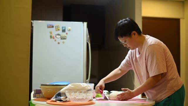 vídeos de stock e filmes b-roll de an asian chinese stay home mother preparing dough - baking bread at home