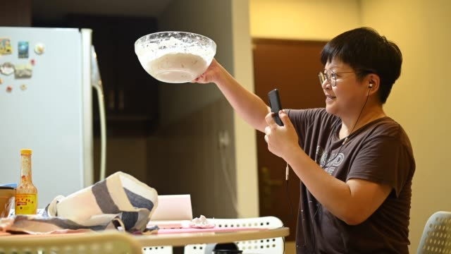 vídeos de stock e filmes b-roll de an asian chinese stay home mother preparing dough while using phone online checking for for recipe and guidance online class - baking bread at home