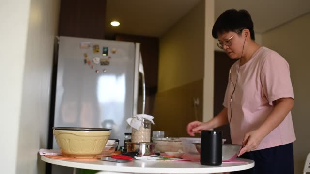 vídeos de stock e filmes b-roll de an asian chinese stay home mother preparing dough while using virtual assistant smart speaker for recipe and guidance - baking bread at home