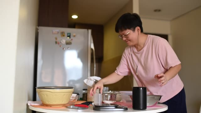 una madre asiatica cinese rimanere a casa preparando pasta mentre si utilizza assistente virtuale altoparlante intelligente per ricetta e guida - assistente virtuale video stock e b–roll
