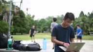 istock an asian chinese teenage boy doing homework using laptop at public park bench while his friends playing basket ball 1267585345
