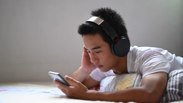 vídeos de stock, filmes e b-roll de um adolescente asiático chinês em casa ouvindo música com seu fone de ouvido durante o fim de semana deitado na cama - 16 17 anos