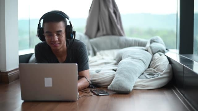 vídeos de stock, filmes e b-roll de um adolescente asiático escola em casa estudando em casa na sala do quarto usando laptop - 16 17 anos