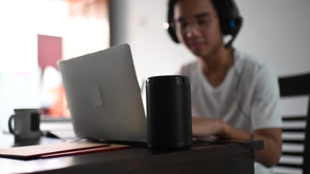 an asian chinese teenager chatting online with all his classmates via online software while doing his homework at the kitchen dining table together with his virtual assistant smart speaker - assistente virtuale video stock e b–roll