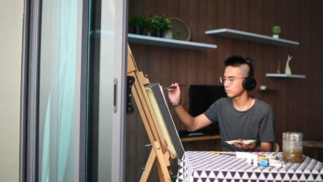 un adolescente cinese asiatico disegno pittura acrilica a casa in soggiorno - pittore video stock e b–roll