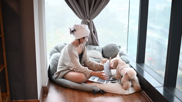 an asian chinese teenager girl surfing the net in her bedroom using her laptop while doing face spa mask with her pets dog and cat