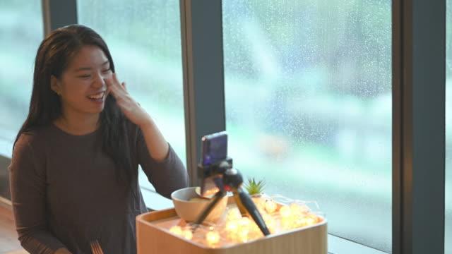 stockvideo's en b-roll-footage met een aziatische chinees tienermeisje dat in haar ruimte vlogging die appel eet gebruikend haar slimme telefoon tijdens het regenen dag het glimlachen - daten