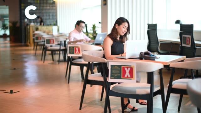 カフェで休憩を取って彼女のデザートを楽しんでいるアジアの中国のホワイトカラー労働者 - カフェ文化点の映像素材/bロール