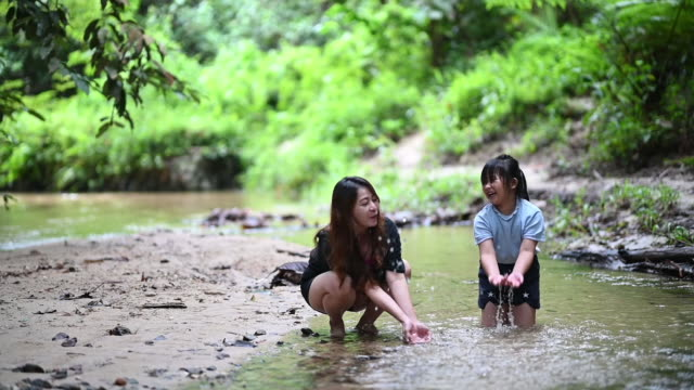 an asian chinese woman having bonding tine with her daughter at the river playing with water splashing - невинность стоковые видео и кадры b-roll