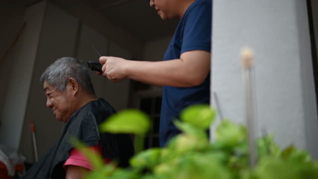 vídeos de stock e filmes b-roll de an asian chinese woman is cutting and trimming her father's hair at front yard of her house during the quarantine period of coronavirus - covid hair