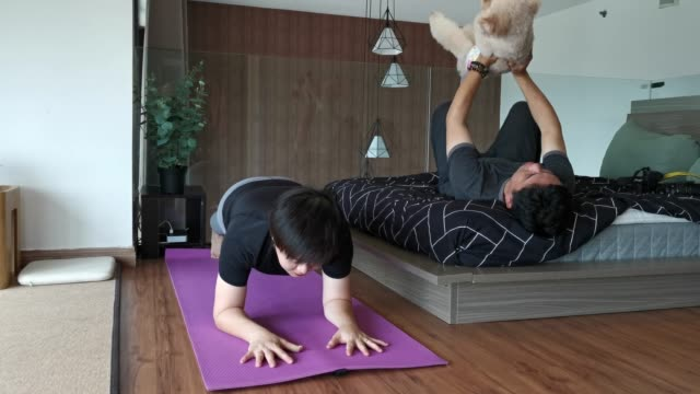 an asian chinese woman workout in bedroom doing plank position while her husband on bed doing push up with their toy poodle pet dog humor