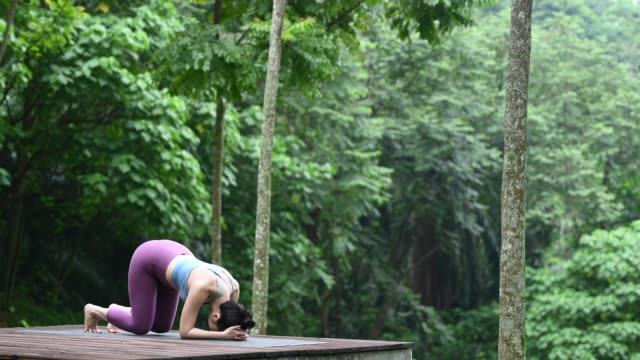 an asian chinese yoga instructor doing a head stand poses in the forest on a wooden platform