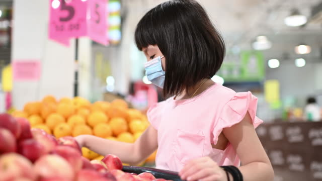 an asian chinese young girl buying fruit in supermarket duriing weekend looking at the fruit peach - pesche bambino video stock e b–roll
