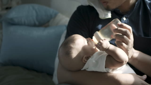 An Asian father milk feed a baby An Asian father milk feed a baby feeding stock videos & royalty-free footage