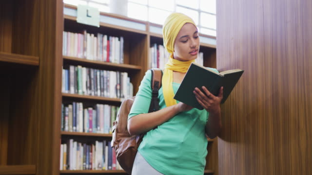 an asian female student wearing a yellow hijab leaning against bookshelves and reading a book - abbigliamento modesto video stock e b–roll