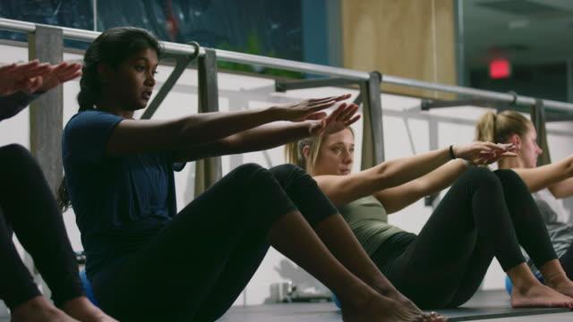 en asiatisk indisk kvinna i tjugoårsåldern med armarna utsträckta utför omväxlande magövningar med en grupp kvinnor på en barre motion studio - balettstång bildbanksvideor och videomaterial från bakom kulisserna