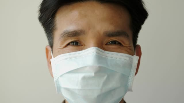 vídeos de stock e filmes b-roll de an asian man wearing a face mask to protect against a disease that is prevalent today. - covid hair