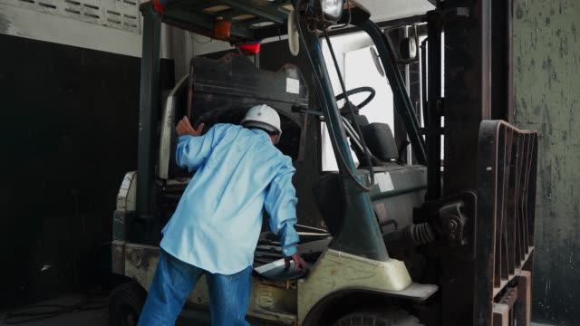 An asian senior engineer checking on a forklift An asian senior engineer or mechanic checking on a forklift in factory forklift stock videos & royalty-free footage