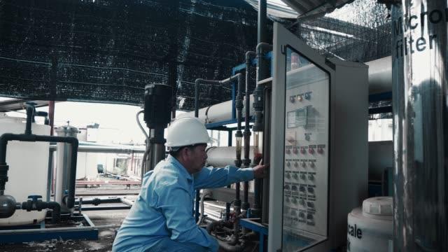 vídeos de stock, filmes e b-roll de um coordenador ou um mecânico sênior asiático usando o gerador de poder da água - eletricista