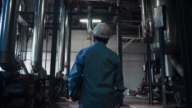 an asian senior engineer or mechanic walking among industrial machine - attrezzatura industriale video stock e b–roll
