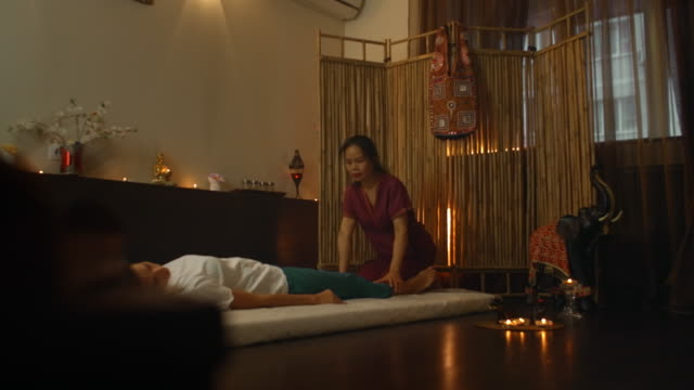 an asian woman performs a traditional thai massage on the back of a lying beautiful european girl. chiropractor produces treatment with alternative methods - cultura tailandese video stock e b–roll