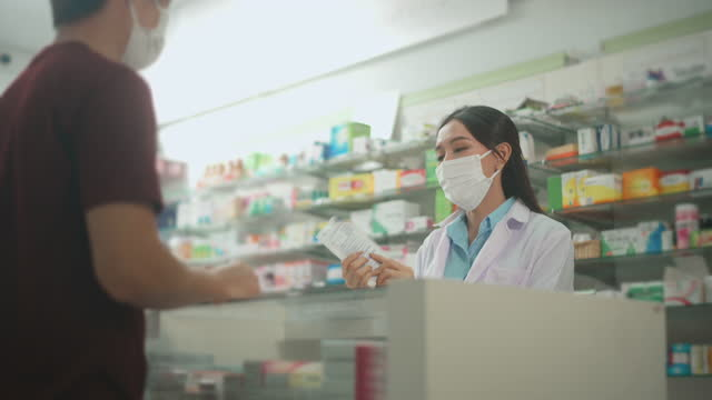 An asian woman pharmacist wearing protective mask and lab coat in a modern pharmacy drugstore, selecting a medicine for customer.